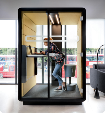 A modern acoustic office pod with height-adjustable tabletop for individual work in standing and sitting position hushWork Hushoffice